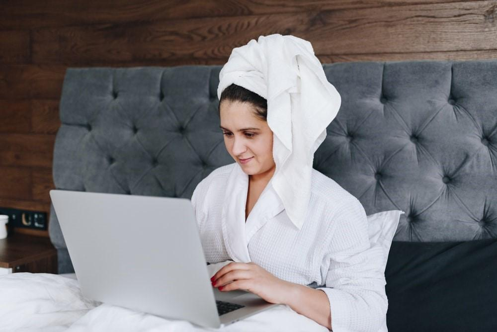 A woman sitting in bed, working on her laptop