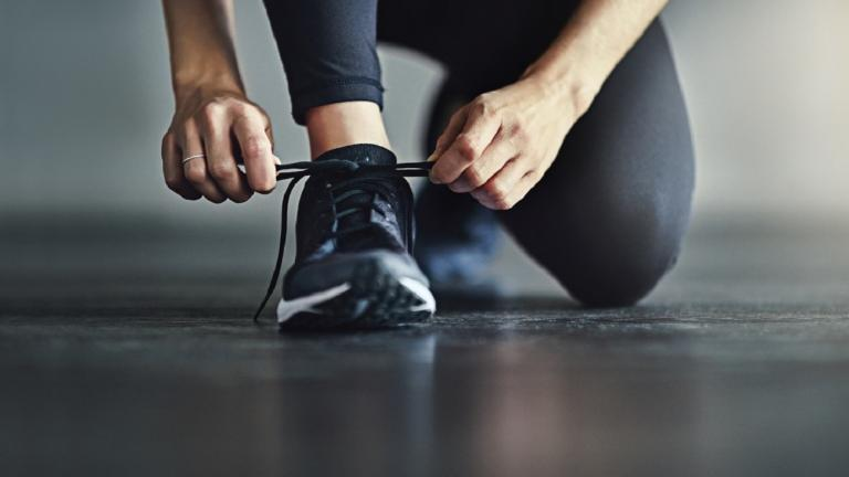 Person doing up shoes about to go running