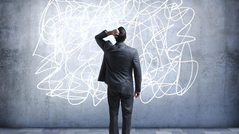 Confused man looks at scribbles on wall