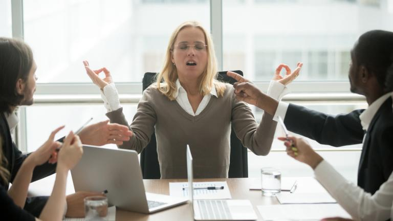 Stressed businesswoman meditating at meeting with diverse employees