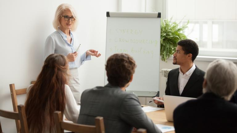 Businesswoman giving presentation at corporate team meeting