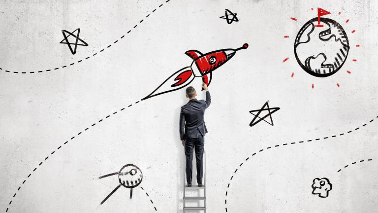 A businessman draws paints a rocket that will reach a goal set on a planet's surface