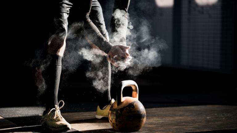 Person in gym lifting kettlebell
