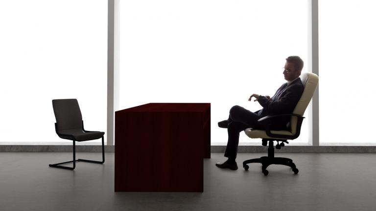 Business man sat at empty desk
