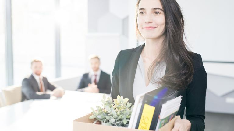 Waist up portrait of smiling young businesswoman holding box of personal belongings leaving office after quitting job