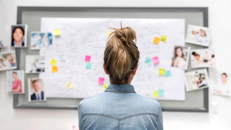 Back of a creative business woman brainstorming at the office using a whiteboard