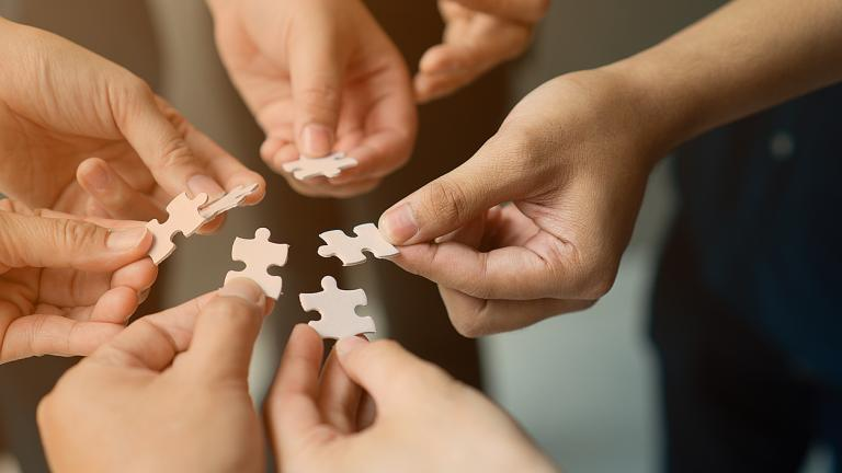 Hands with jigsaw join together as team