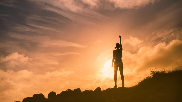 woman celebrating at the top of a mountain, motivation and achievement