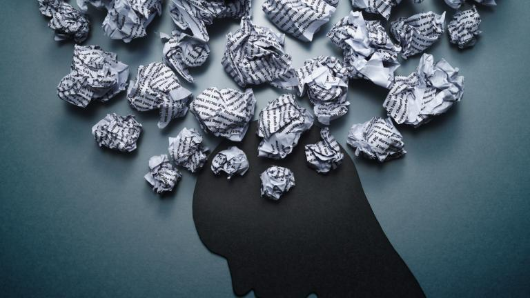 Concept image of depression and anxiety. Waste paper and head silhouette.