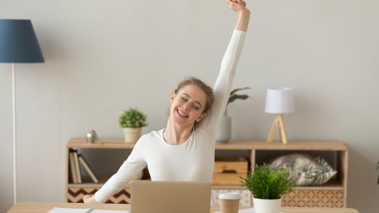 Happy satisfied young woman sitting at the desk in office room or home at workplace finish work, stretching out with raised hands