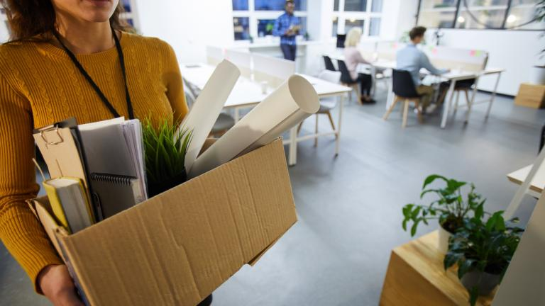 Serious sad woman in sweater carrying cardboard box full of stuff and leaving office after dismissal