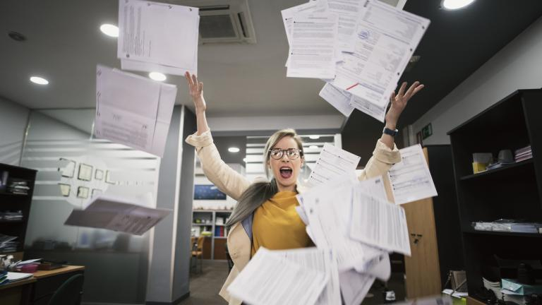 woman throws papers in the office in an image of relief
