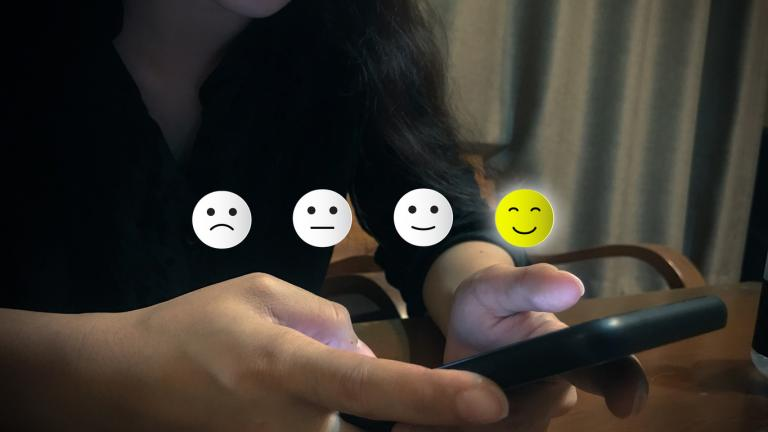 Customer experience concept. A woman using smartphone choose happy smile face icon. Depicts that customer is very satisfied.