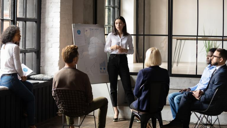 Confident lady business trainer coach leader give flip chart presentation consulting clients teaching employees