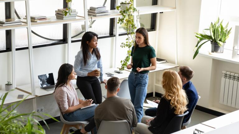 diverse office employees gather together in modern light co-working space