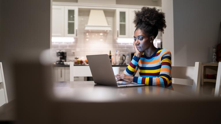 woman working from home on a laptop at her kitchen table