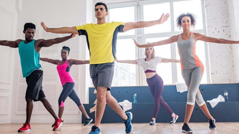 Low angle view of handsome trainer performing zumba with multicultural dancers in studio