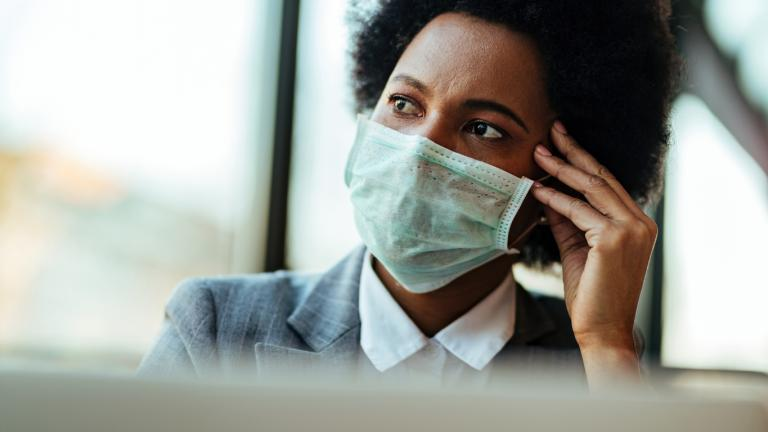 business woman wearing suit and mask looking worried