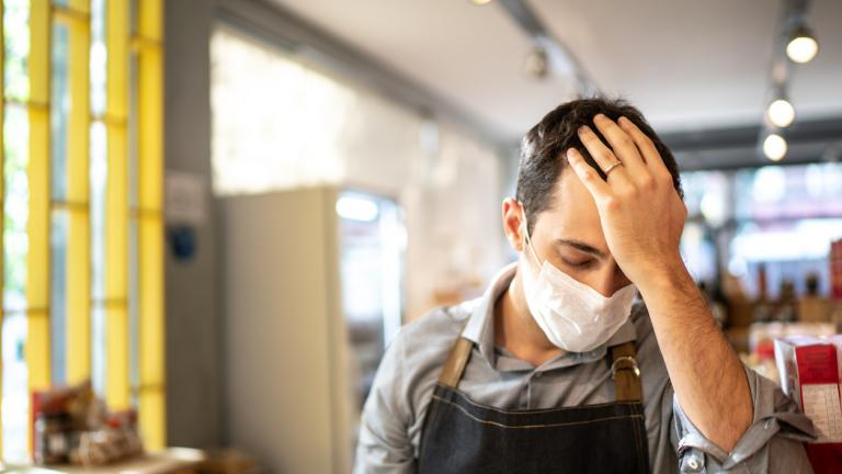 Worried owner with face mask at his small business