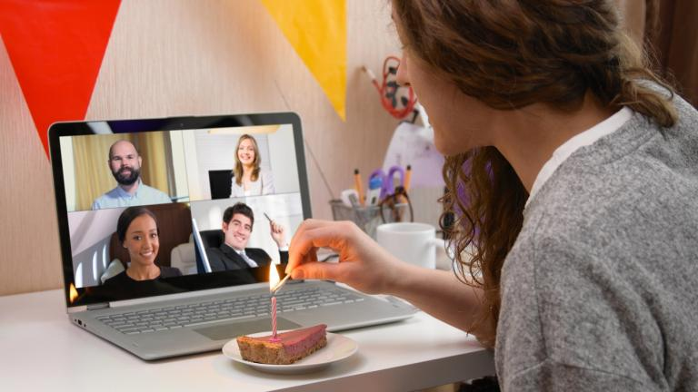 Woman celebrating her birthday through video call virtual party with friends. Lits and blows out candle. Authentic decorated home workplace.