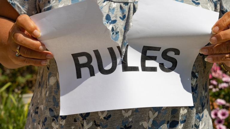 A female tearing up a printed sign that says RULES