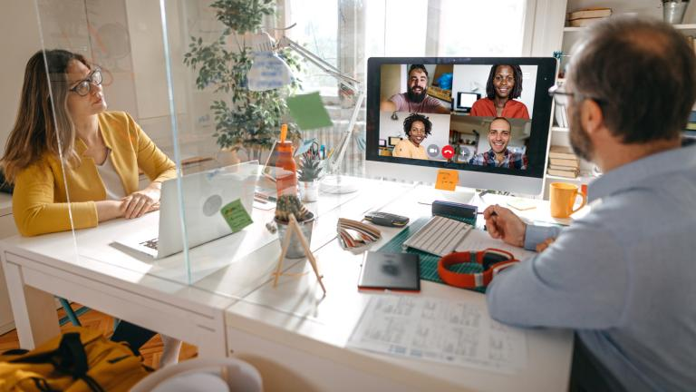 Businessman and businesswoman discussing work on video call with team members through glass partition at office