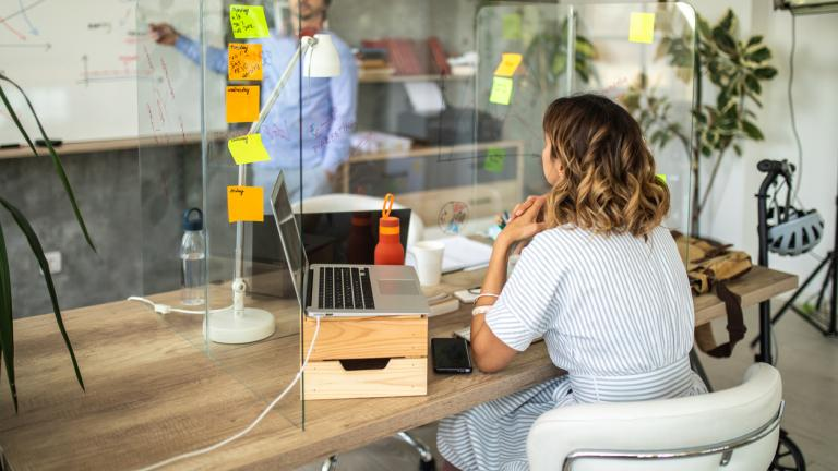 Socially distanced office with perspex screens Manager standing in front of whiteboard and discussing about business strategy with his female coworker