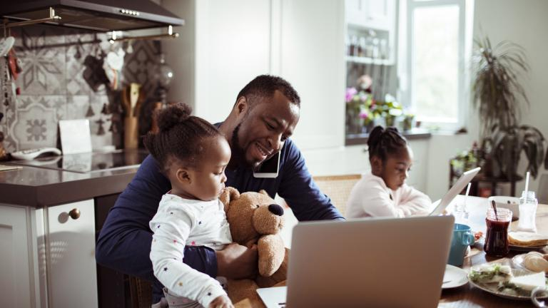 Close up of a young family using a laptop in the morning , while the father is talking on the phone
