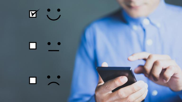 Businessman holding digital smartphone with a checked box on Excellent Smiley Face Rating for a Satisfaction Survey, Customer Experience Concept.