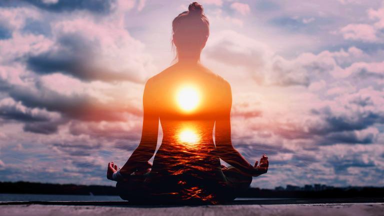 Spiritual Woman practicing lotus asana at sunset.