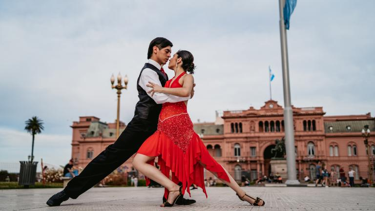 Young Latin couple dancing tango on Plaza de Mayo square in Buenos Aires, Argentina.