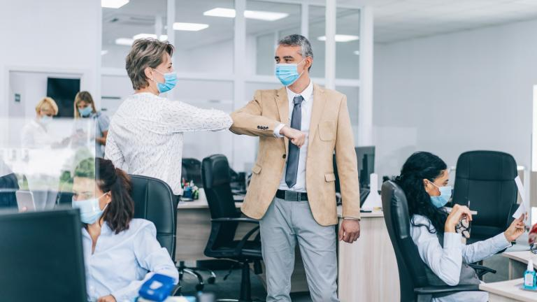 Colleagues in the office practicing alternative greeting for safety and protection during COVID-19