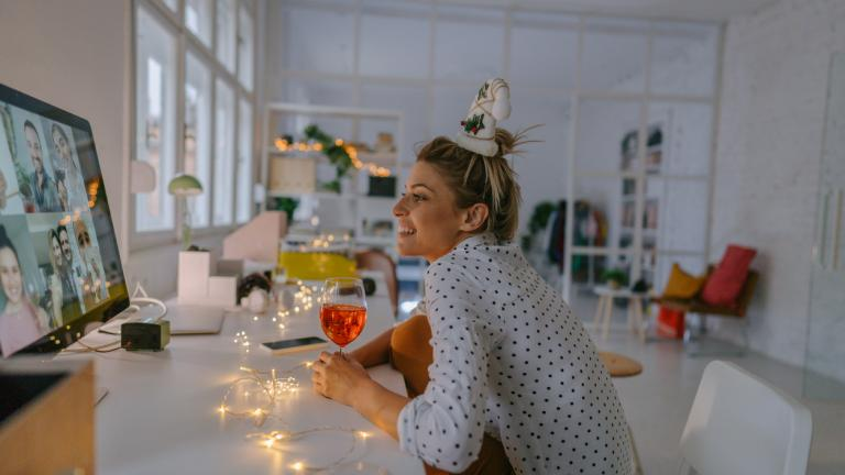 Photo of a young woman celebrating Christmas by having a virtual Christmas party with her friends