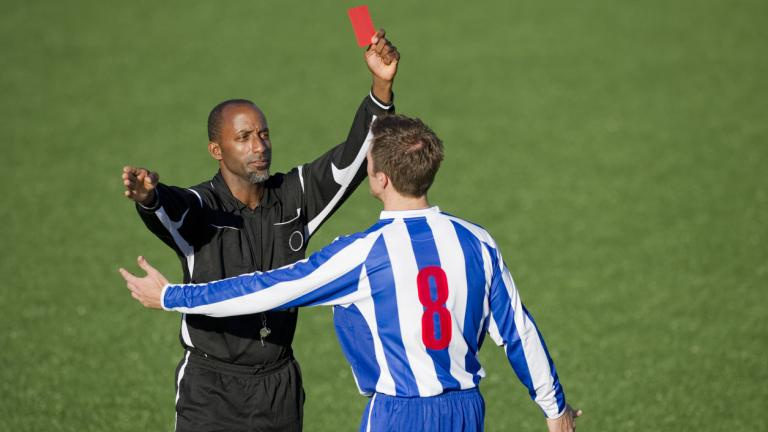 football referee giving red card to player