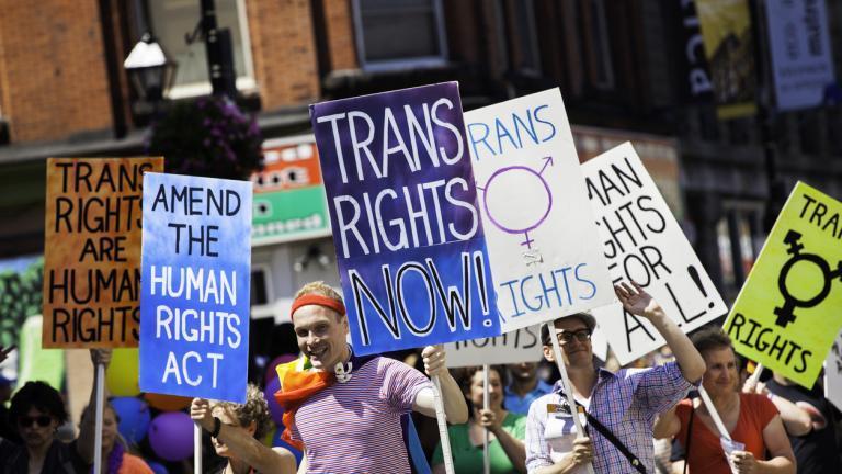 protestors holding signs advocating for transgender rights