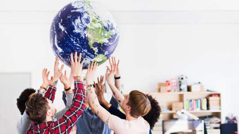 Young start-up business team playing with inflatable earth globe in their office.