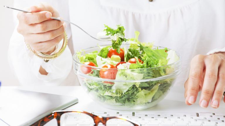 woman eating salad at desk