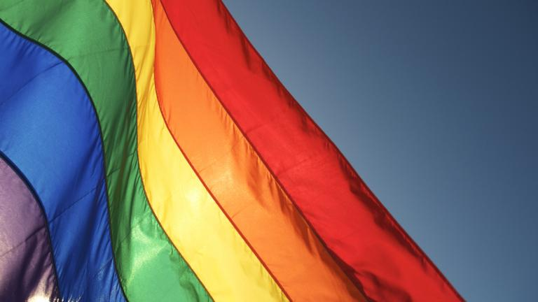 Rainbow flag glows in bright sun waving in blue sky. Some motion blur on top edge of waving flag.