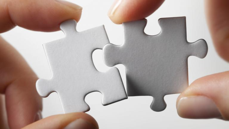 Connection. Hands trying to fit two puzzle pieces together