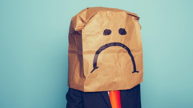 Businessman wears paper bag with sad face drawn on it