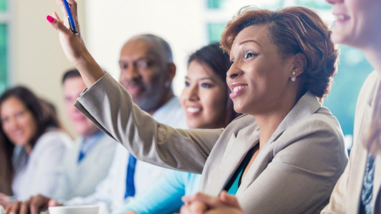 woman raising her hand to ask a question during a training session