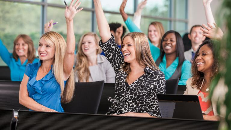 Female college students or business women in an auditorium style classroom with tiered seating, enthusiastically raising their hands, eager to answer a question.