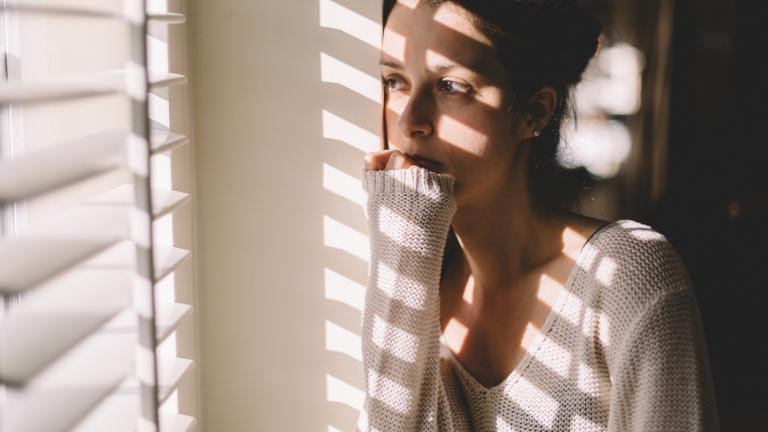 sad woman looking out of her window at home
