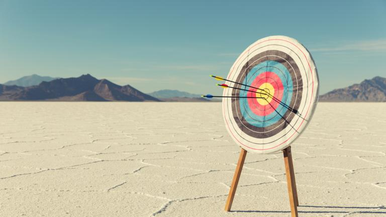 A target with several arrows in the bullseye stands on the Bonneville Salt Flats