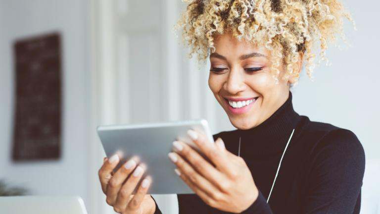 Beautiful afro american young woman using a digital tablet in an office, receiving good news, smiling. Close up of face.