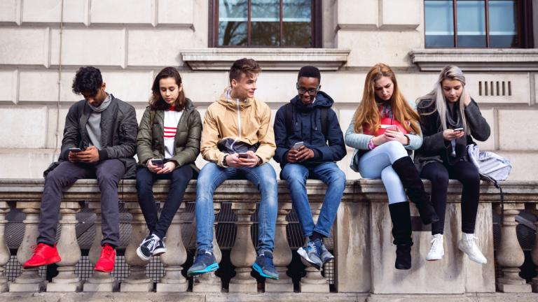Group of young teenagers students using smartphone on a school break