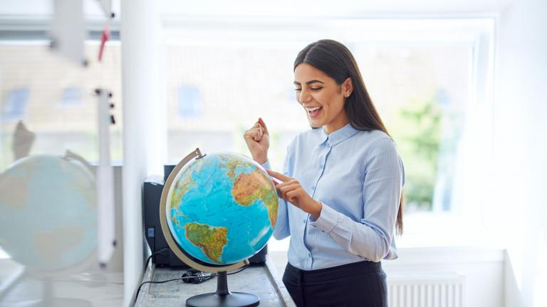 woman in office looking at globe