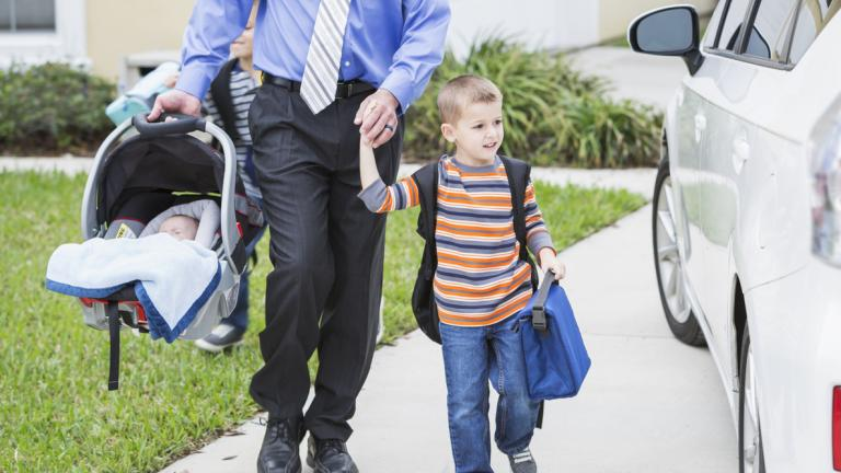 Businessman with baby taking son to school