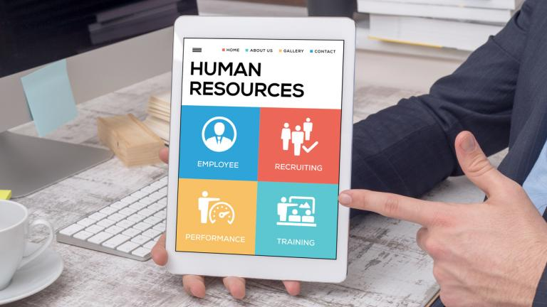 ipad showing the core areas of HR on a display, held by a business man's hand on a work desk