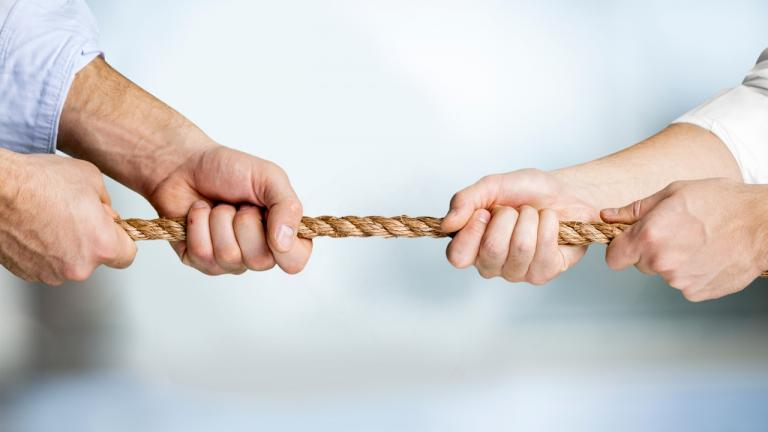 conflict image - two pairs of hands holding a rope at either end